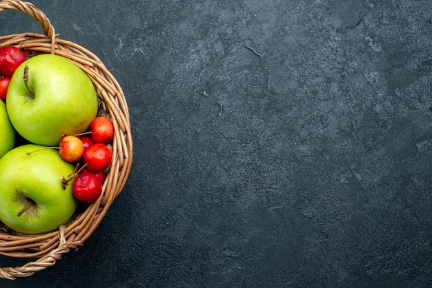 Top view basket with fruits apples and sweet cherries on dark background fruit berry composition freshness
