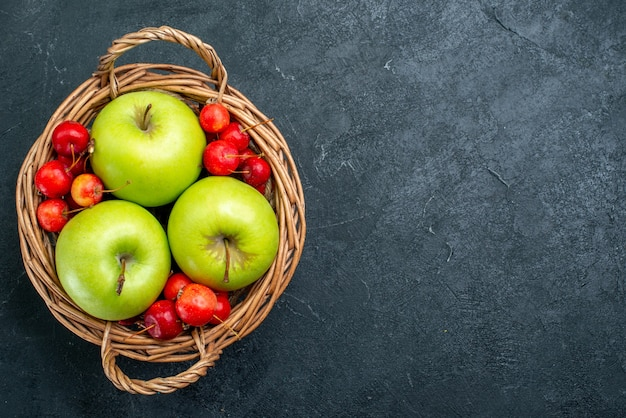 Top view basket with fruits apples and sweet cherries on dark background fruits berry composition freshness tree plant