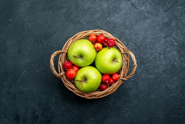Top view basket with fruits apples and sweet cherries on dark surface fruits berry composition freshness tree