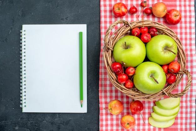Il canestro di vista superiore con le mele verdi della frutta e le ciliege dolci sulla superficie grigio scuro fruttifica l'albero dolce di freschezza della composizione