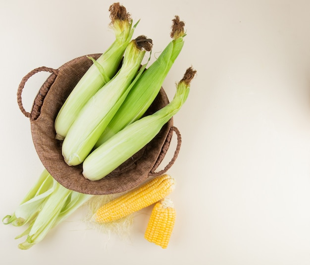 Top view of basket with uncooked corns and corn shell with cooked corns on right side and white surface with copy space