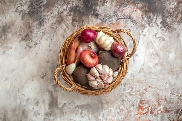 Вид сверху корзина с овощами, чесноком, луком и свеклой на легком спелом салате фото диета