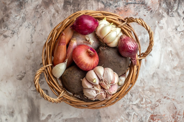 Top view basket with vegetables garlics onions and beet on light color ripe salad photo diet