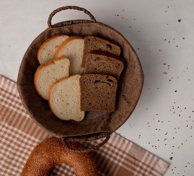 Top view of basket with white and rye bread slices and bagel on cloth on white background with copy space