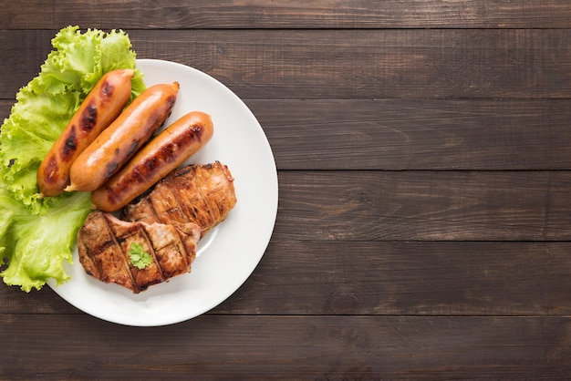 Top view bbq grilled meat, sausages and vegetables on dish on wooden background. copy space for your text