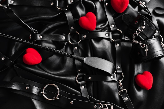 Top view of bdsm leather kit against of a black silk.