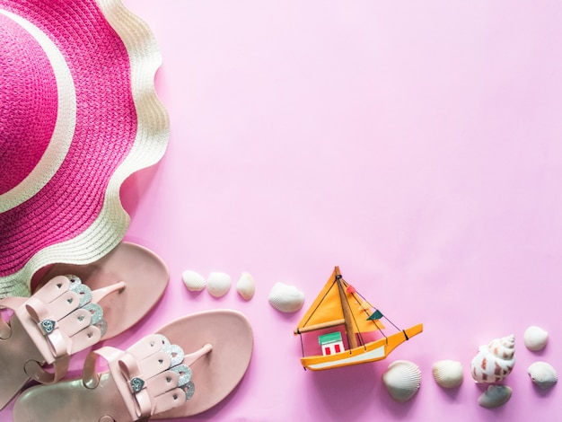 Top view: beach accessories on pink background.