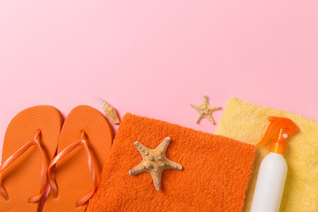 Top view of beach flat lay accessories. sunscreen bottle with seashells, starfish, towel and flip-flop on colored background with copy space.