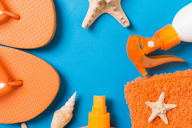 Top view of beach flat lay accessories. sunscreen bottle with seashells, starfish, towel and flip-flop on colored background with copy space