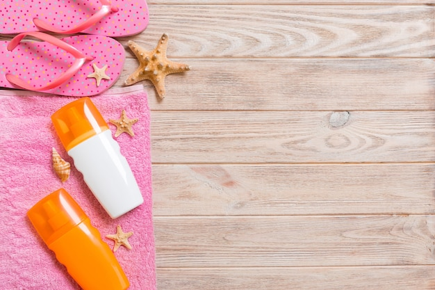 Top view of beach flat lay accessories. sunscreen bottle with seashells, starfish, towel and flip-flop on wooden board background with copy space.