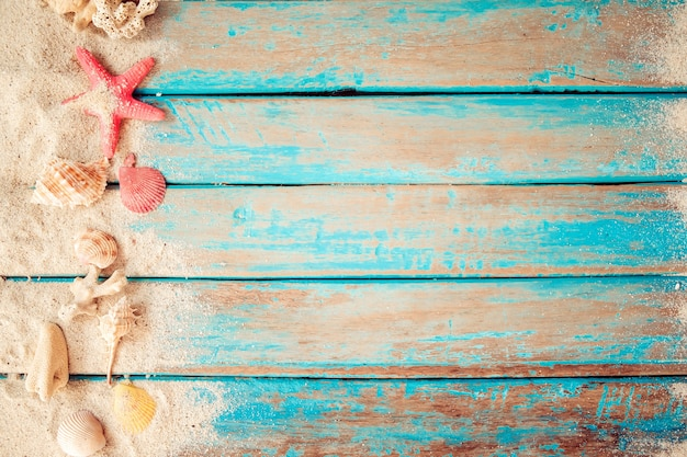 Top view of beach sand with shells, starfish on wood plank in blue sea paint
