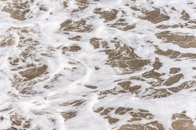 Top view of beach with water and foam