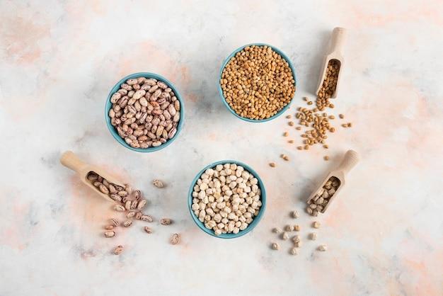 上面図白い表面上のボウルに豆、パスタ、ひよこ豆。