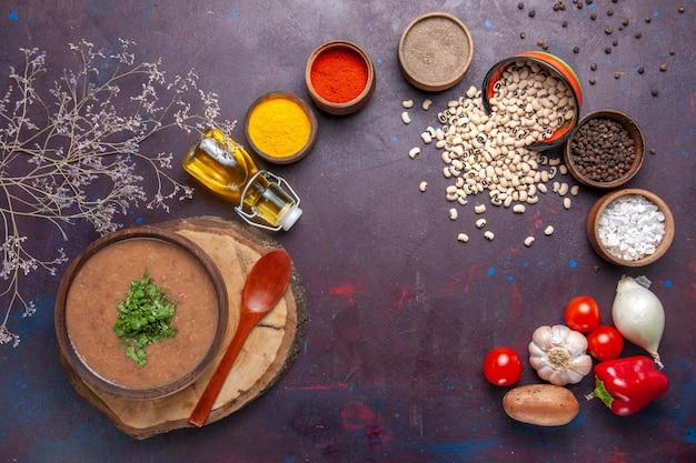 어두운 책상에 조미료와 함께 상위 뷰 콩 수프 맛있는 요리 수프 수프 콩 색 매운 식사