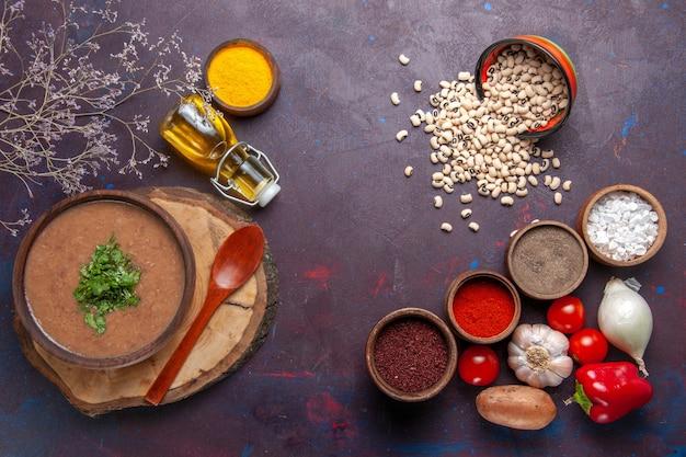 상위 뷰 콩 수프 어두운 표면에 조미료와 함께 맛있는 요리 수프 수프 콩 색 매운 식사