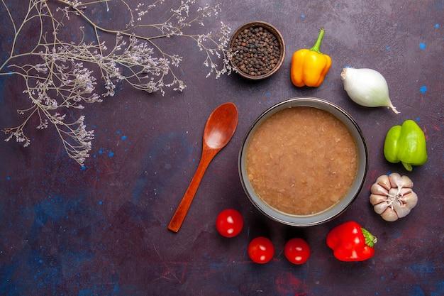 Вид сверху фасолевый суп с оливковым маслом и овощами на темной поверхности суп из фасоли