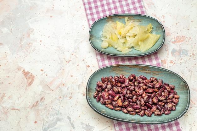 楕円形のプレートに豆とピクルスのキャベツを上から見る