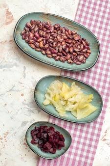 Vista dall'alto fagioli cavolo sottaceto barbabietola tagliata su piatti ovali