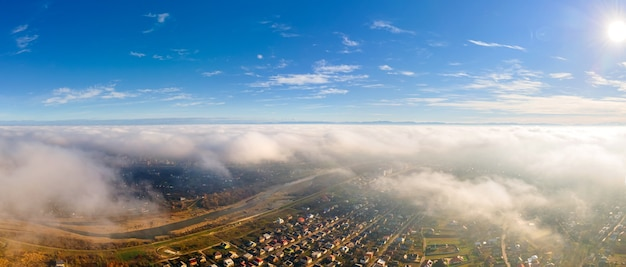 Top view of beautiful blue sky with clouds and view residential buildings near fields.