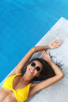 Top view of beautiful brunette woman with golden summer tan, lying near swimming pool and smiling in sunglasses and bikini.