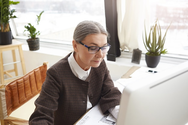 Top view of beautiful elderly woman architect on retirement working on construction project in home office, making drawings, filling in electronic specification on computer. freelance concept