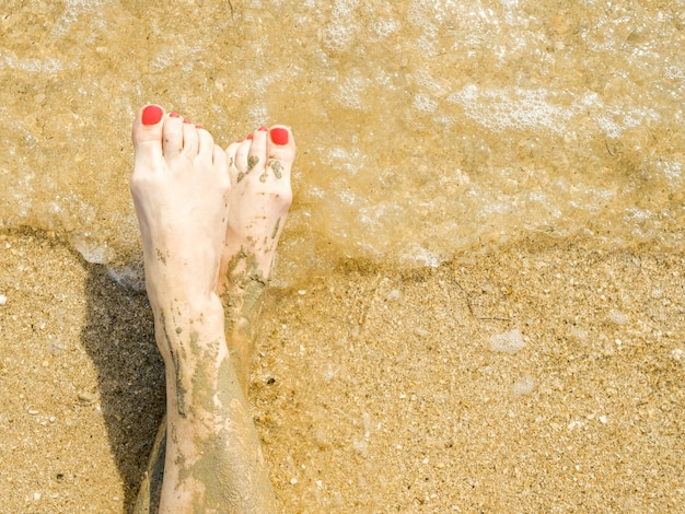 Top view of beautiful female feet with bright red pedicure on the sand of the beach