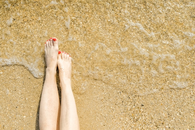 Top view of beautiful female feet with red pedicure on the sand of the beach near the water