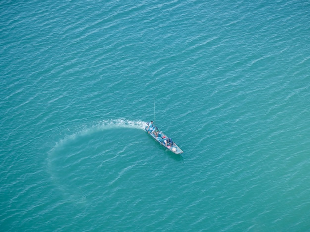 Top view of beautiful fishing boats on the sea and clear water.