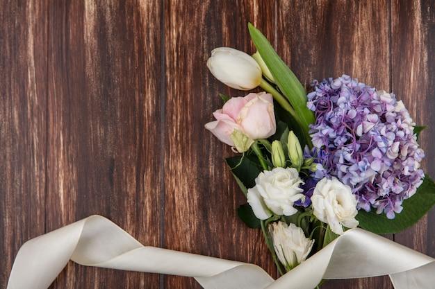 Vista dall'alto di bellissimi fiori come gardenzia tulipano e rose isolate su uno sfondo di legno con spazio di copia