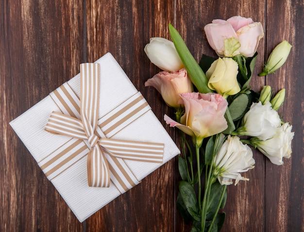 Vista dall'alto di bellissimi fiori come tulipani e rose con confezione regalo isolato su uno sfondo di legno