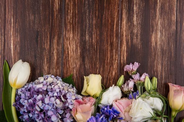Vista dall'alto di bellissimi fiori come le rose tulipano gardenzia isolate su uno sfondo di legno con spazio di copia