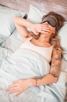 Vista dall'alto della bella notte che dorme con la maschera per gli occhi in camera da letto.