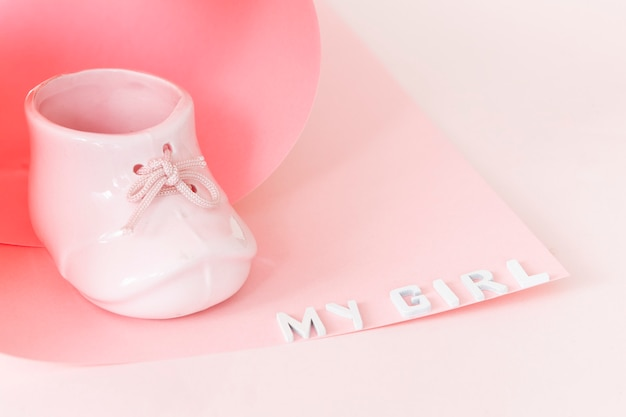 Top view of beautiful porcelain mug pink baby shoe shape and my girl letters in paper swirl