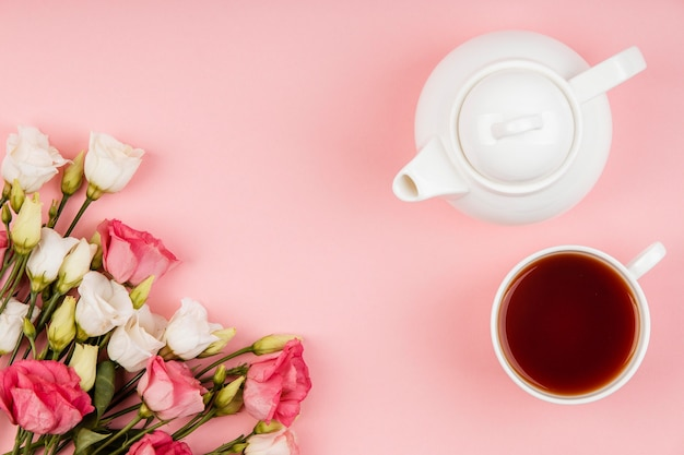 Вид сверху красивая композиция из роз с чайником и чашкой чая