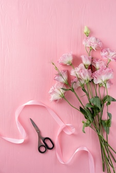 Vista dall'alto di bellissime rose con forbici e nastro