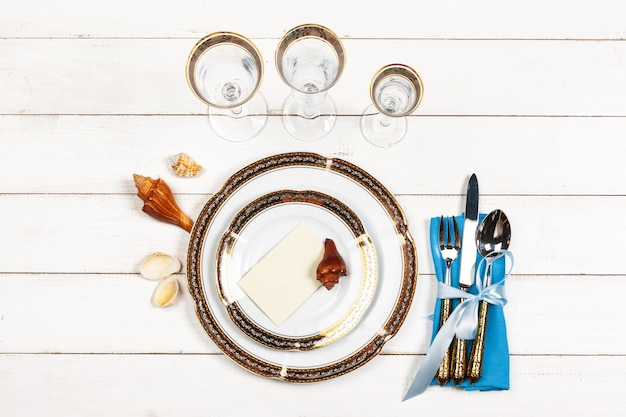 Top view of a beautiful table setting on white wooden background