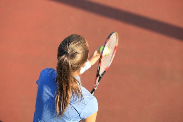 Top view of beautiful tennis player ready to serving the ball on the tennis court.