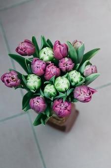 Top view of beautiful tulip flowers in vase on the floor
