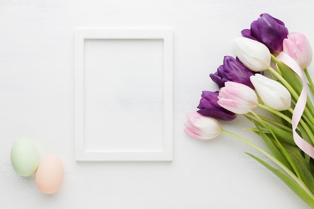 Top view of beautiful tulips with frame and easter eggs