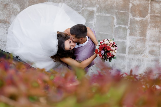 Top view of beautiful wedding couple with wedding bouquet who are kissing outdoors, marriage concept