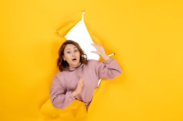 Vista dall'alto di una bella donna che guarda qualcosa con espressione facciale sorpresa e spazio libero su giallo strappato