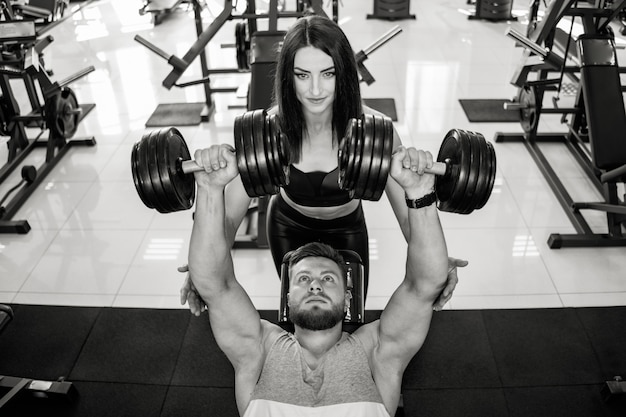 Top view of a beautiful woman in sportswear helping strong man to lift dumbbells. black and white photo of a beautiful couple in sports gym exercising with dumbbells.