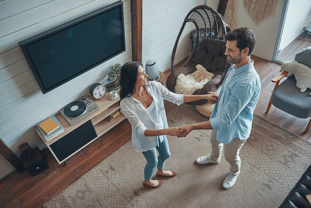 Top view of beautiful young couple smiling and dancing while spending time at home