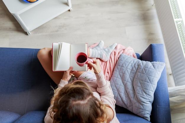 Vista dall'alto di bella giovane donna che tiene tazza di tè mentre ci si rilassa sul divano a casa. mattina calda e accogliente.