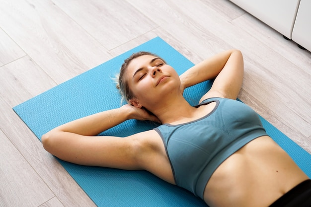 Top view of beautiful young woman lying on yoga mat after workout