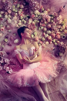 Top view of beautiful young woman in pink ballet tutu surrounded by flowers