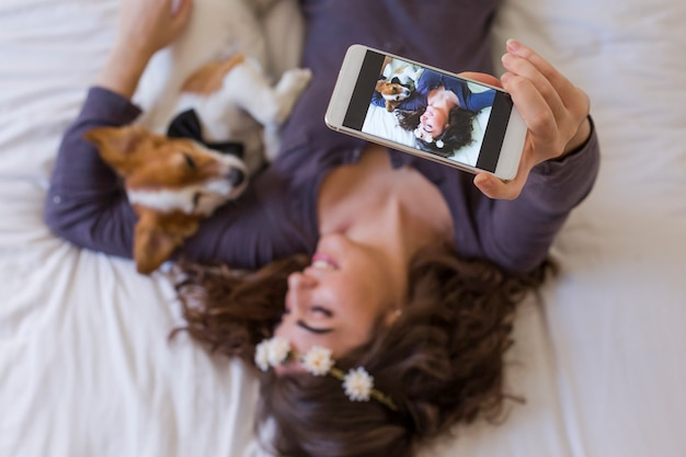 Top view of a beautiful young woman taking a selfie with mobile phone on bed with her cute small dog besides. home, indoors and lifestyle