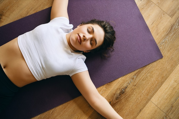 Top view of beautiful young woman in white crop top lying in shavasana or corpse posture during yoga class, resting after practice, meditating, breathing deeply. relaxation and rest concept