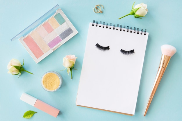 Top view beauty cosmetics with notebook
