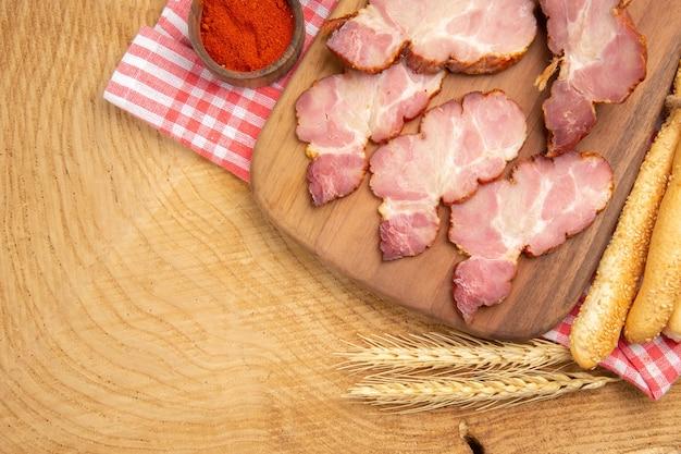 Fette di becon vista dall'alto su tavola di legno peperone rosso in una ciotola spiga di grano pane